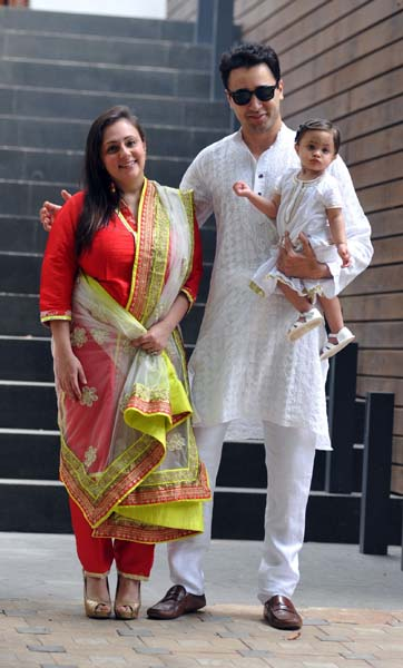 Indian Bollywood actor Imran Khan (C), with his wife Avantika Malik and baby, celebrates and wishes his fans Ramzan Eid Mubarak at his residence in Mumbai on July 18, 2015. AFP PHOTO